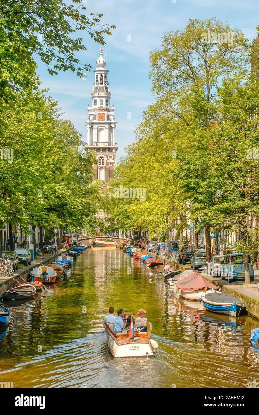 Petit bateau à moteur dans un canal d'eau à Amsterdam, Pays-Bas avec l'Oude Kerk en arrière-plan Banque D'Images