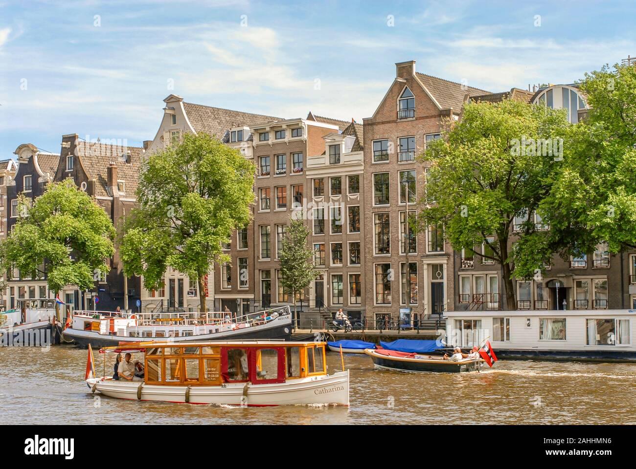Bateau touristique typique dans un canal d'eau à Amsterdam, Pays-Bas Banque D'Images