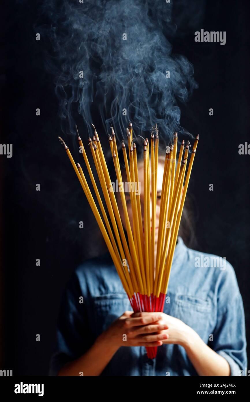 Jeune femme chinoise en priant avec de grands bâtons d'encens brûlant dans ses mains, Ha Chuong Hoi Quan Pagode, Ho Chi Minh City, Vietnam, l'Indochine, l'Asie Banque D'Images