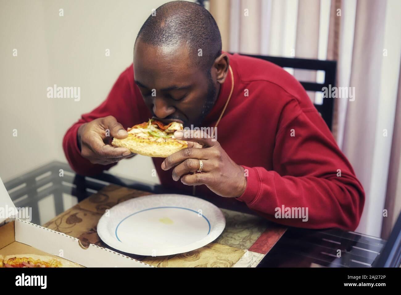 L'homme afro-américain de manger une tranche de pizza à la maison Banque D'Images