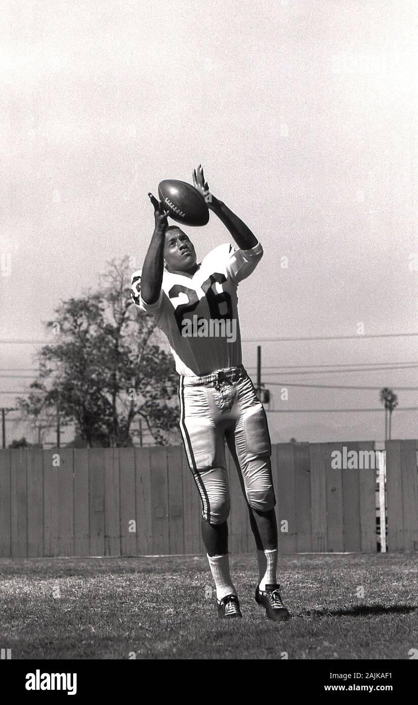 1964, historiques, football américain, homme college student practicising à l'extérieur avec la balle , USA. Banque D'Images