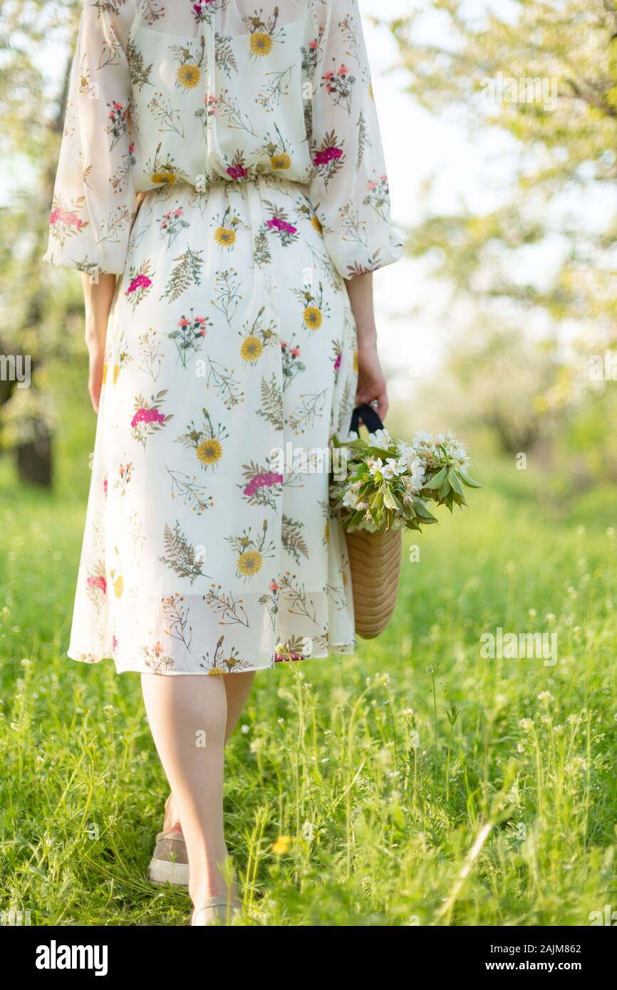 Une fille marche dans un parc vert printemps profiter de la nature en fleurs. Banque D'Images