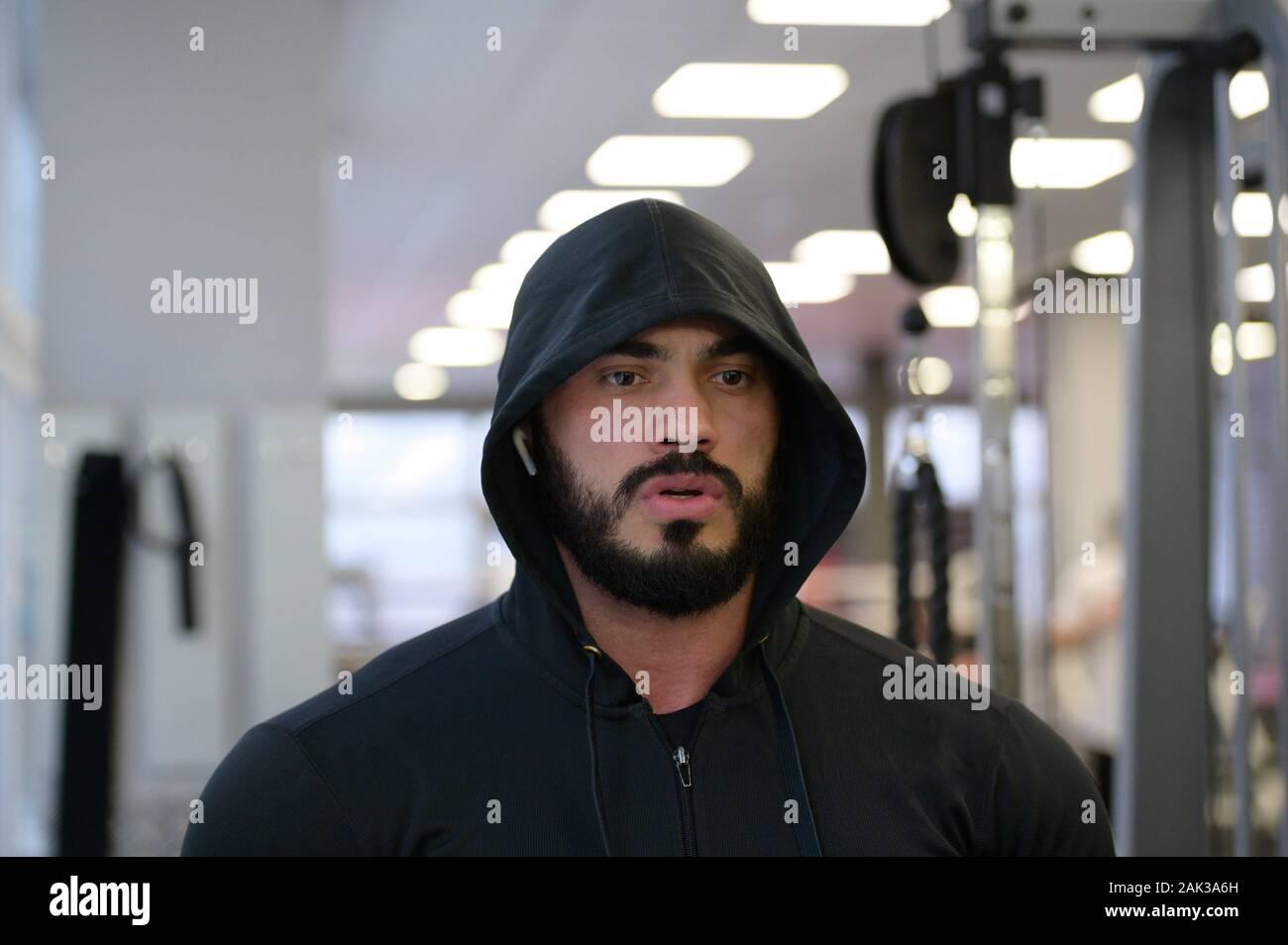Motivation sport concept de jeune homme barbu in hoodie dans fitness sport avec l'esprit de concentration mentale Banque D'Images