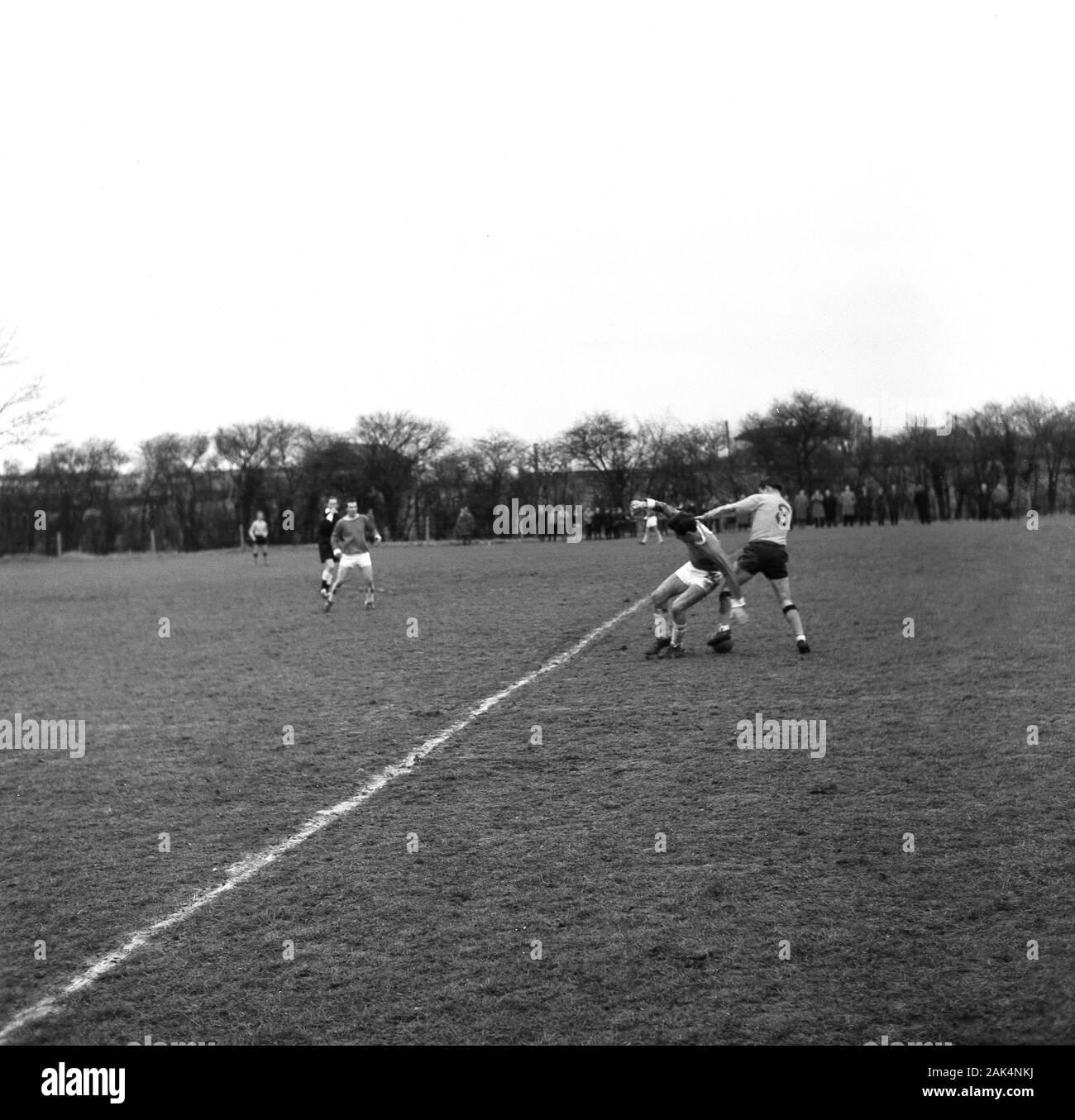 Années 1960, historiques, les footballeurs amateurs jouant sur un terrain boueux d'herbe typique de l'époque, Angleterre, Royaume-Uni. Banque D'Images