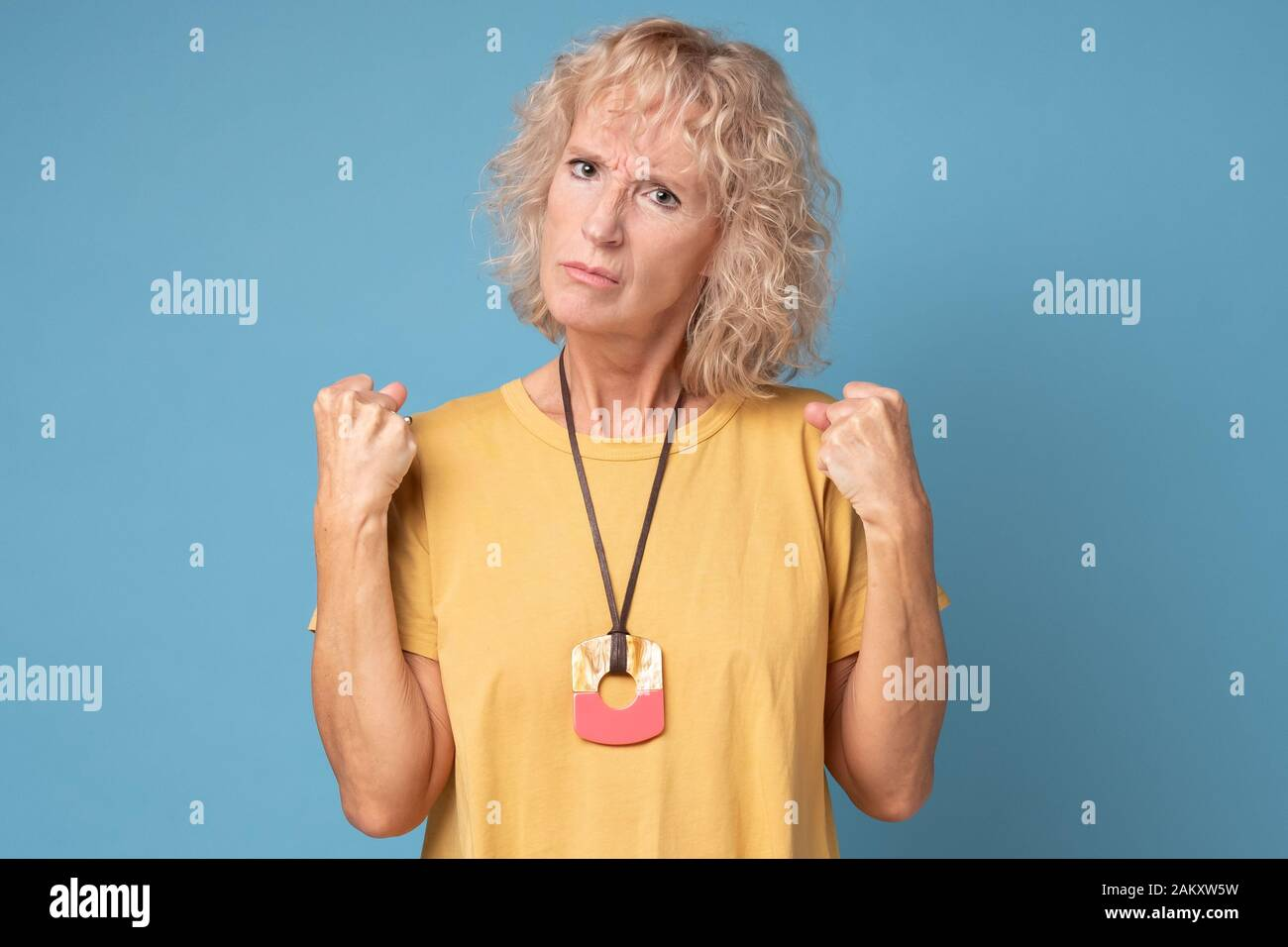 Une vieille femme en colère qui prépare les poings à se défendre sur fond bleu Banque D'Images