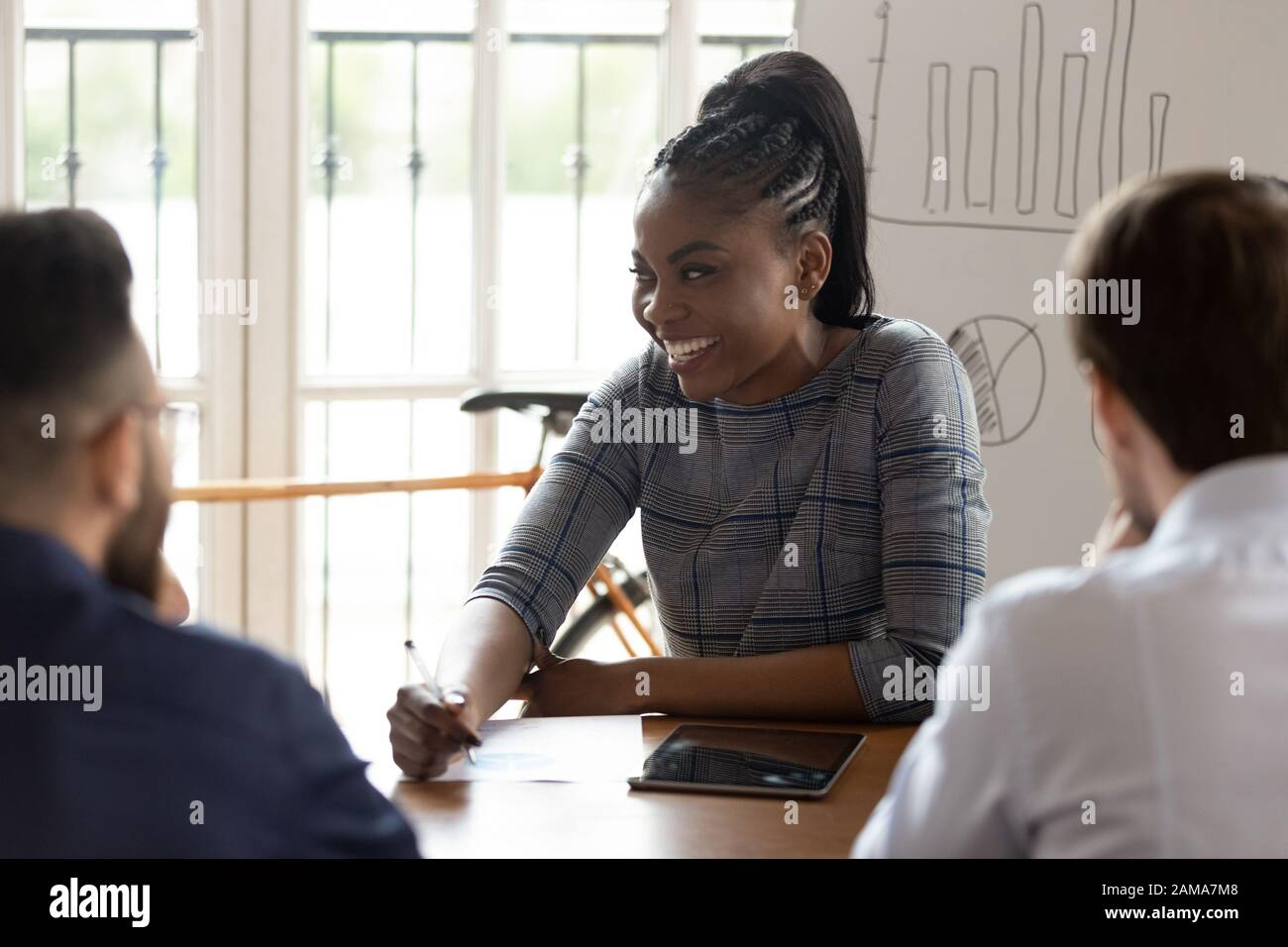 Une femme africaine souriante interagit avec ses collègues lors de la réunion Banque D'Images