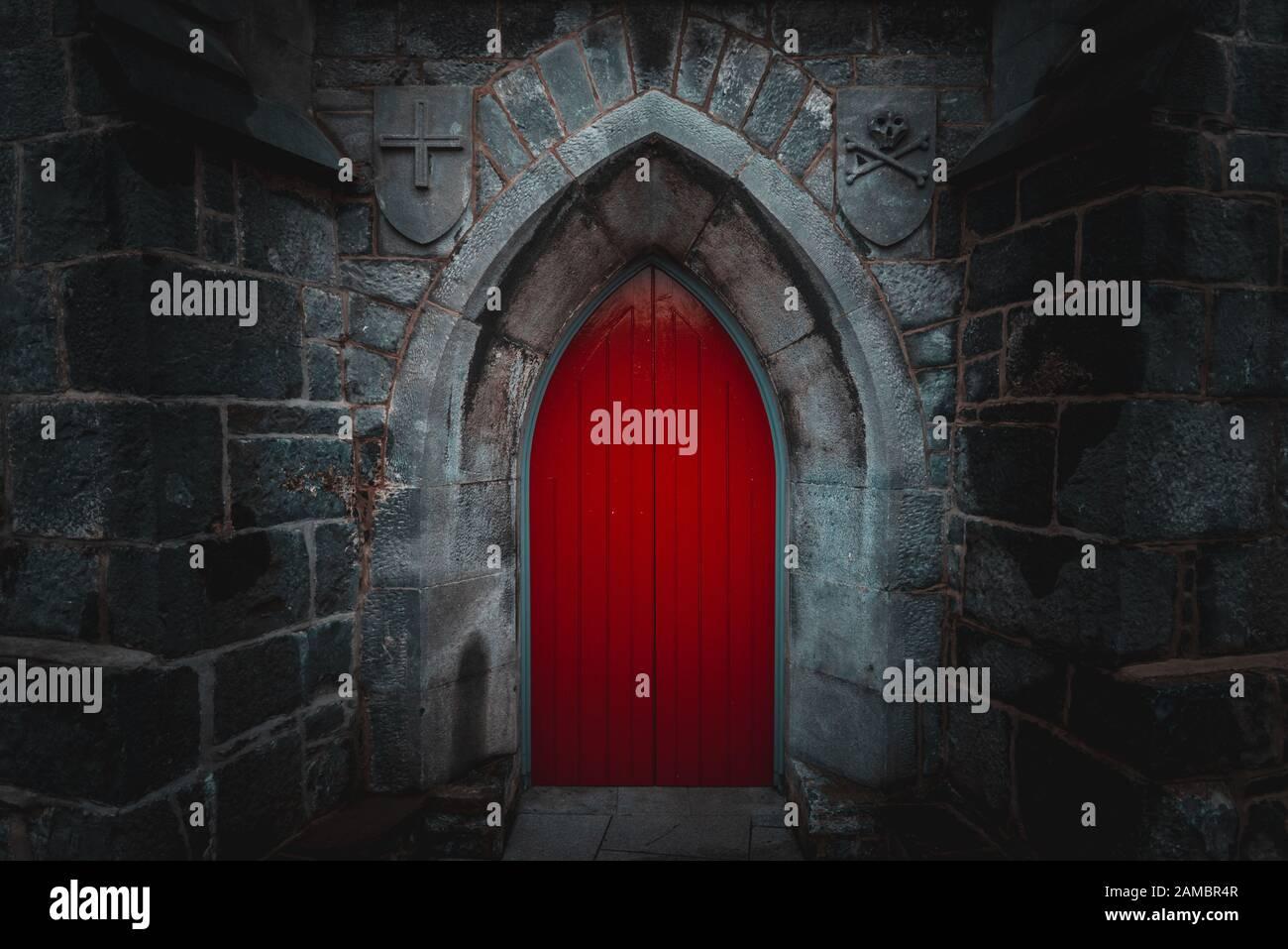 Porte en bois rouge pointu effrayant dans un vieux mur de pierre humide et bâtiment avec cross, du crâne et des os des deux côtés. Mystère, la mort et la notion de danger. Banque D'Images