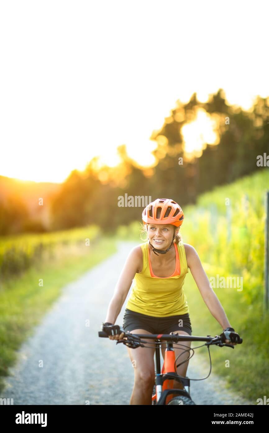 Jolie jeune femme cycliste sur un vélo de montagne bénéficiant d'un mode de vie actif sain en plein air en été (shallow DOF) Banque D'Images