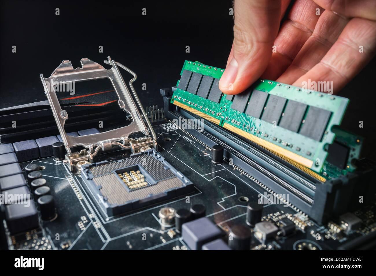 Installation d'une nouvelle mémoire RAM DDR pour un support de processeur d'ordinateur personnel dans un service. Réparation de mise à niveau. Concept de mise à niveau ou de réparation de PC. Banque D'Images
