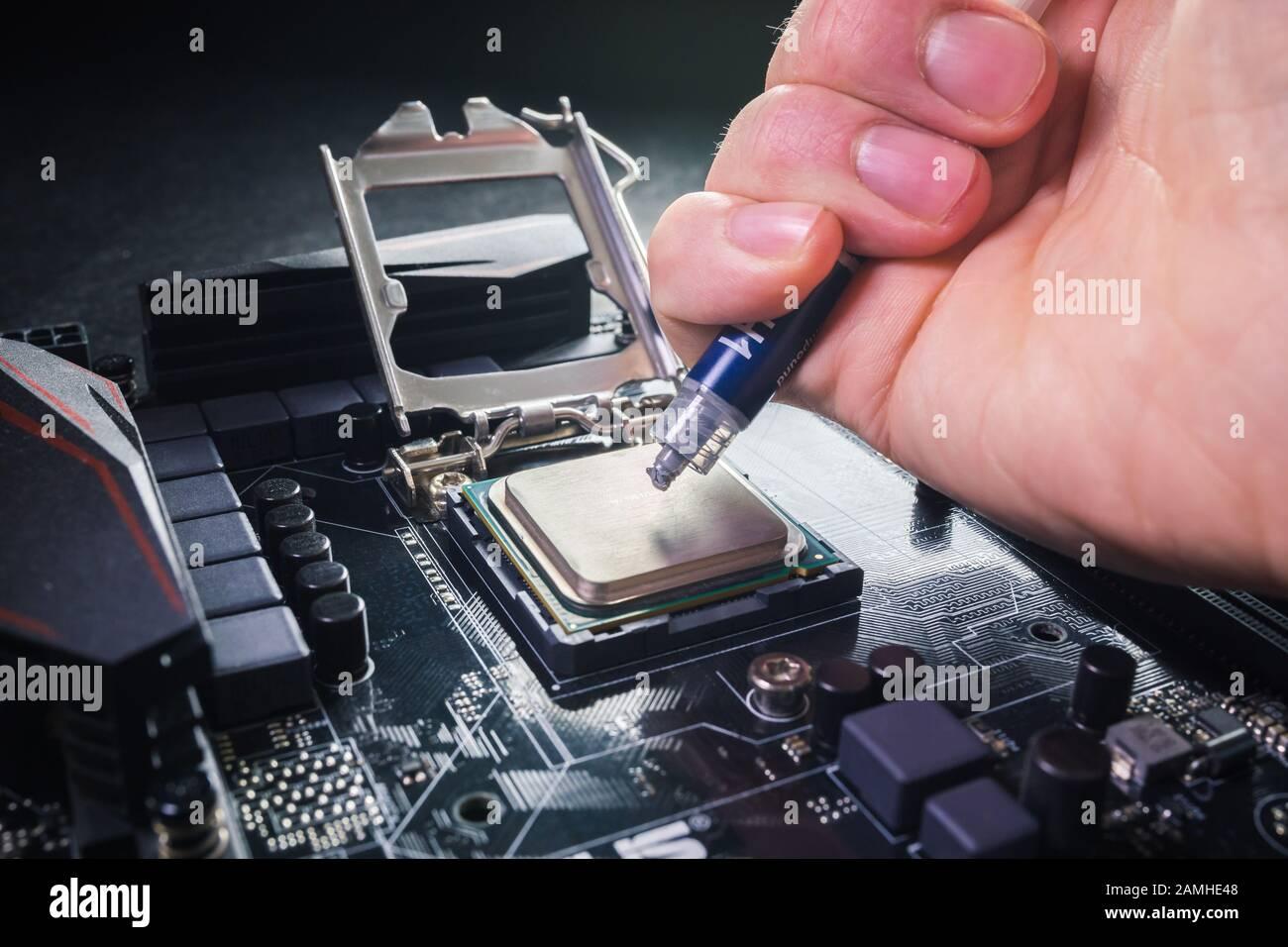 Gros plan jusqu'à ce que le technicien appuie ou application du composé de pâte thermique sur le dessus de la cpu principale dans le support. Concept de réparation ou de mise à niveau Banque D'Images
