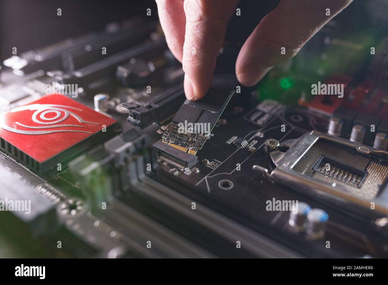 Concentrez-vous sur l'emplacement SSD, tapez M.2 avec prise en charge de NVME, sur la carte mère de l'ordinateur. Le technicien installe un nouveau disque rapide haute capacité avec puces flash Banque D'Images