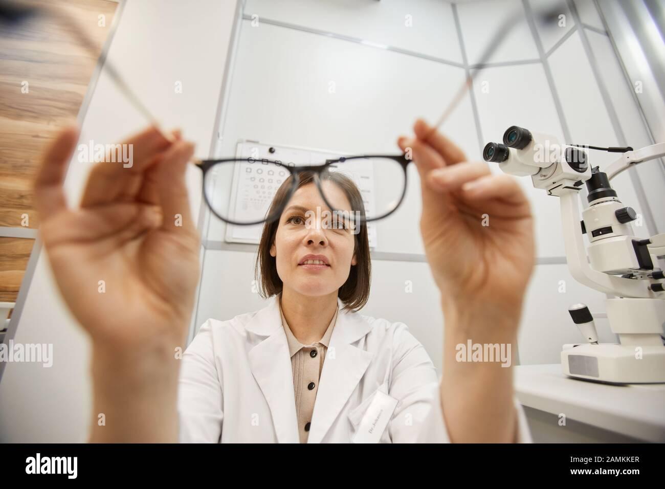 POV shot de jeune optométriste féminin mettant sur des lunettes sur un patient non reconnaissable pendant le test de vision dans la clinique moderne d'ophtalmologie, espace de copie Banque D'Images