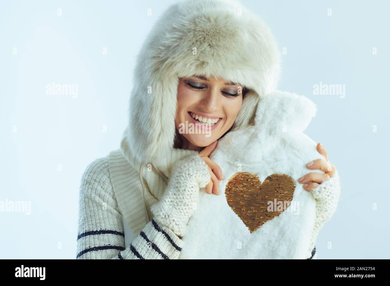 femme souriante et élégante, sweat-shirt à rayures blanches, écharpe et rabats pour les oreilles bonnet embrassant un joli chauffe-eau chaud isolé sur fond bleu clair d'hiver Banque D'Images