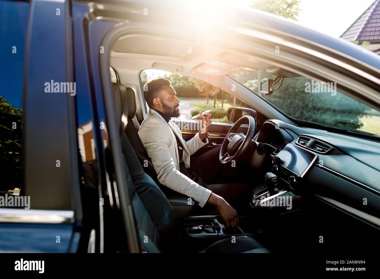 Young handsome African businessman using mobile phone, parlant sur le haut-parleur, tout en étant assis à l'intérieur d'une voiture de luxe Banque D'Images