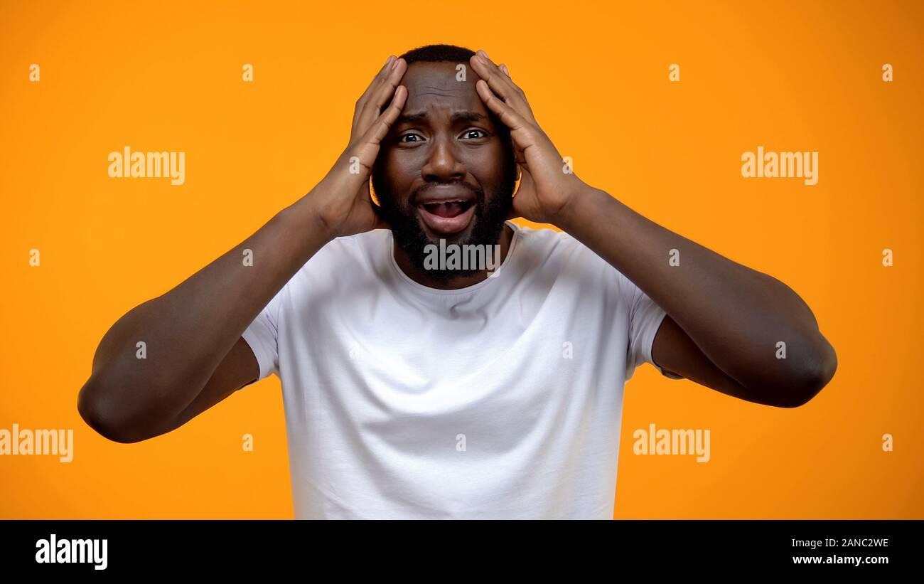 L'homme afro-américain choqué holding head, problèmes de la vie, de mauvaises nouvelles, les commères Banque D'Images