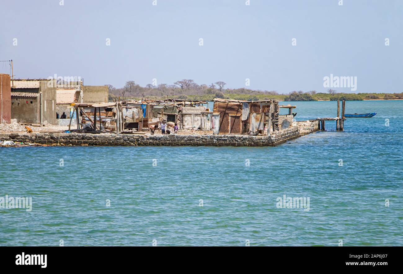 Fadiouth, Sénégal, AFRIQUE - 26 avril 2019: Les garçons sénégalais non identifiés devant les maisons ruinées dans le village de Fadiouth, il y en a peu Banque D'Images