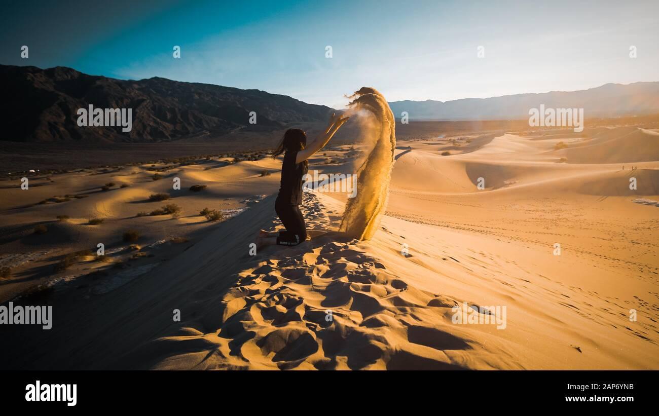 Fille jetant du sable sur les dunes de sable de Mesquite dans le Parc National de la Vallée de la mort, Californie, États-Unis Banque D'Images