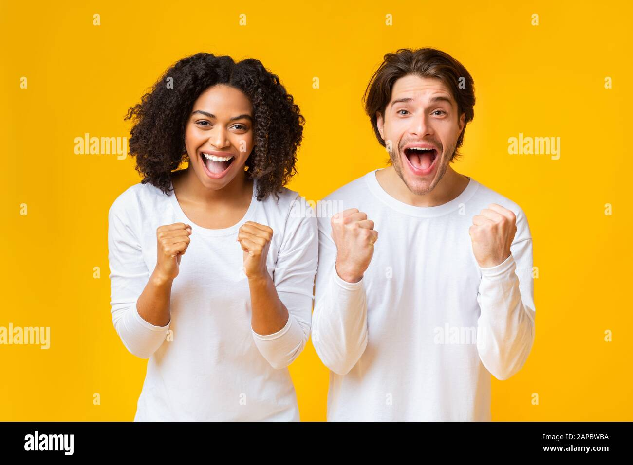 Un couple de race mixte à Cheful célébrant le succès, se levant les mains avec enthousiasme Banque D'Images