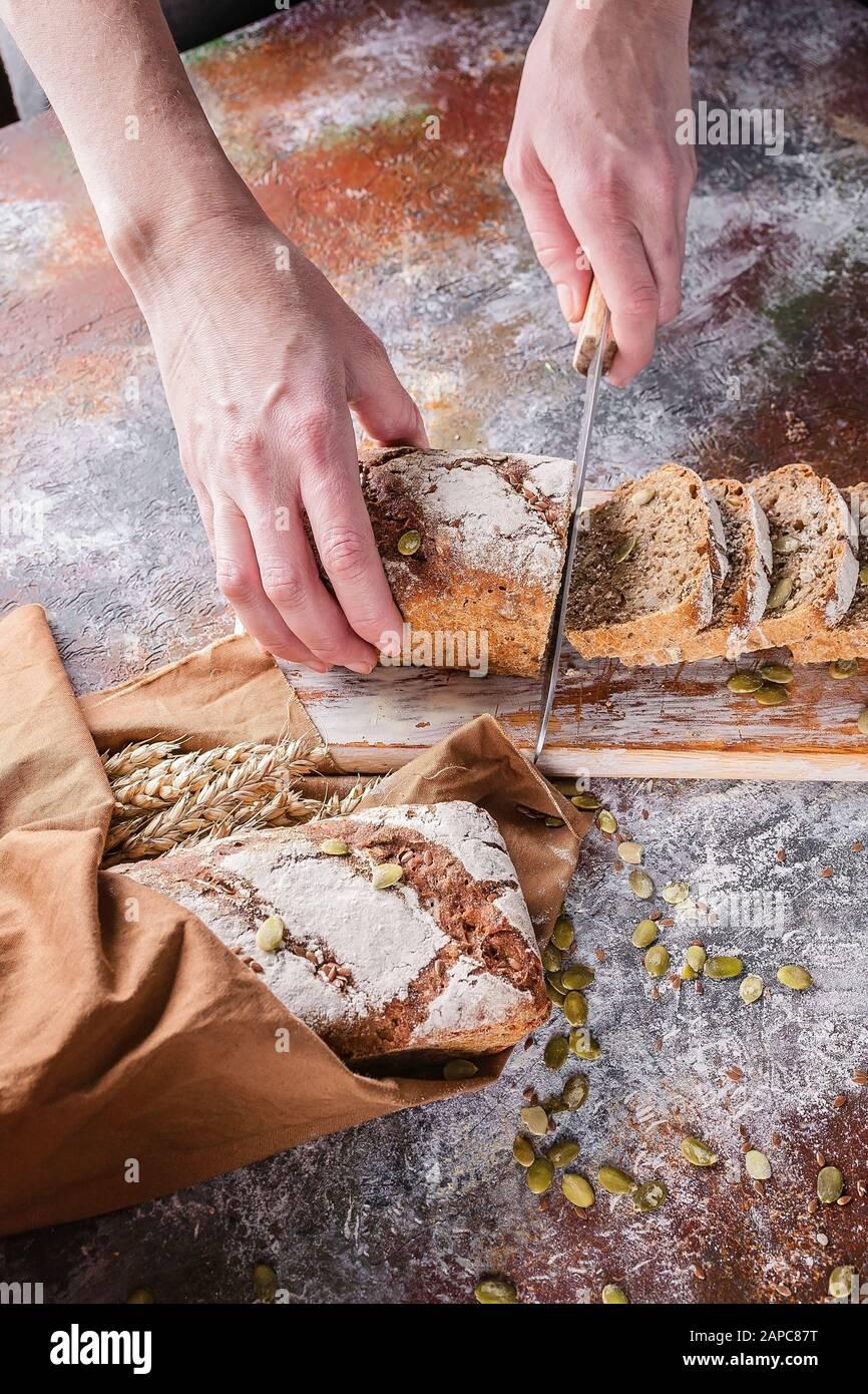 Les mains femelles à photo verticale coupent du pain de levain fraîchement cuit avec des graines de tournesol et de citrouille sur une serviette brune. Oreilles de blé. Banque D'Images