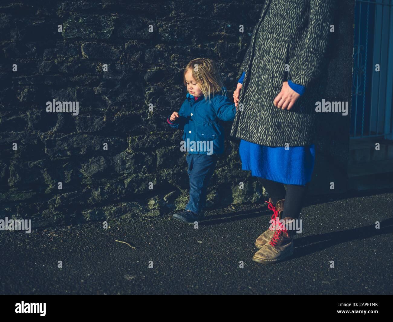 Une jeune mère et son tout-petit tiennent les mains pendant qu'ils marchent en hiver Banque D'Images