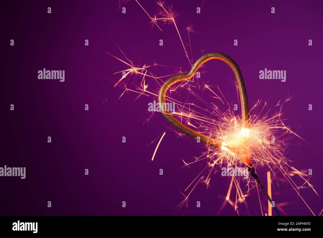 Brûlant le sparkler en forme de coeur d'amour sur un fond violet avec beaucoup d'étincelles. Célébration de la Saint-Valentin. Banque D'Images