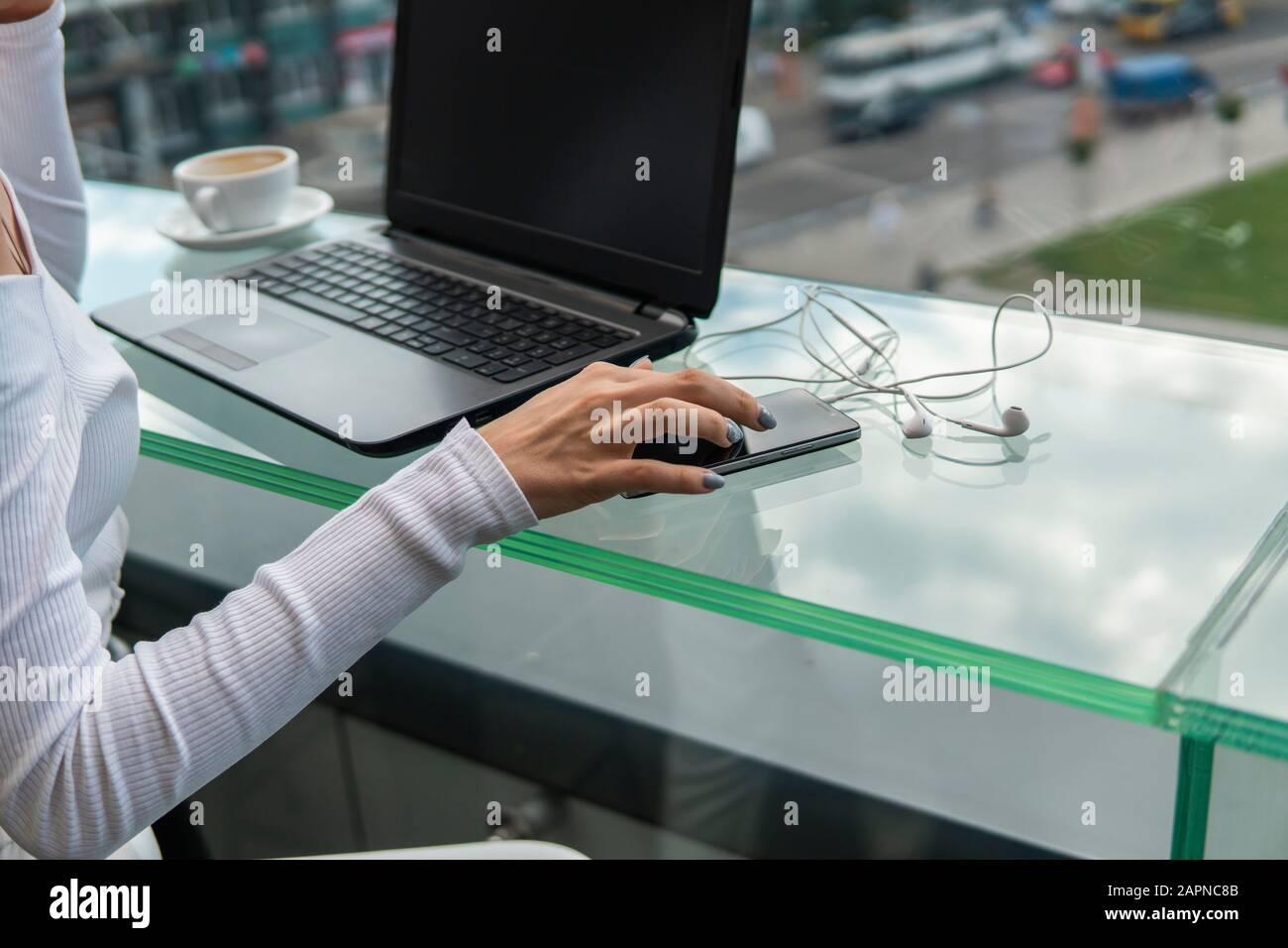 Une femme travaille à l'aide d'un ordinateur portable sur la table. Mains de la saisie sur un clavier. Femme d'affaires est de taper sur un clavier d'ordinateur portable assis dans le café. Banque D'Images