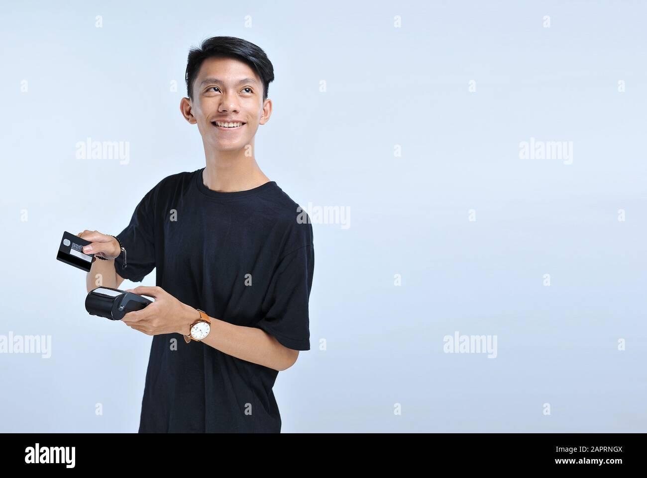 Jeune homme asiatique balayez une carte de crédit / une carte de débit et en regardant l'espace de copie isolé sur le fond gris Banque D'Images