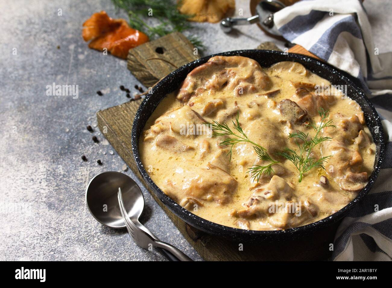 Fricasse - Cuisine Française. Poulet cuit dans une sauce crémeuse aux champignons dans une poêle sur fond de pierre légère. Banque D'Images
