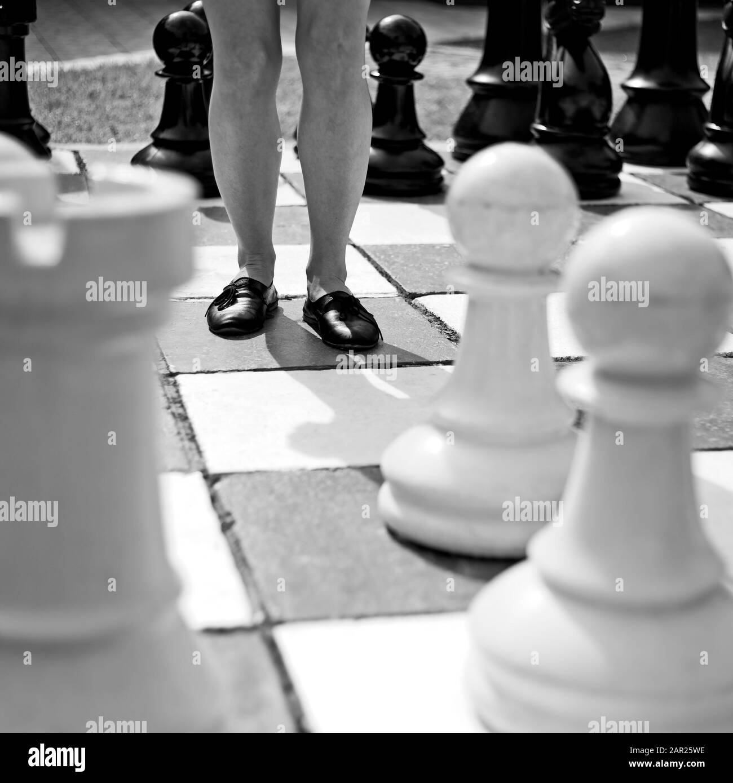 Cliché en échelle de gris d'une femelle debout au milieu d'un grand jeu d'échecs Banque D'Images