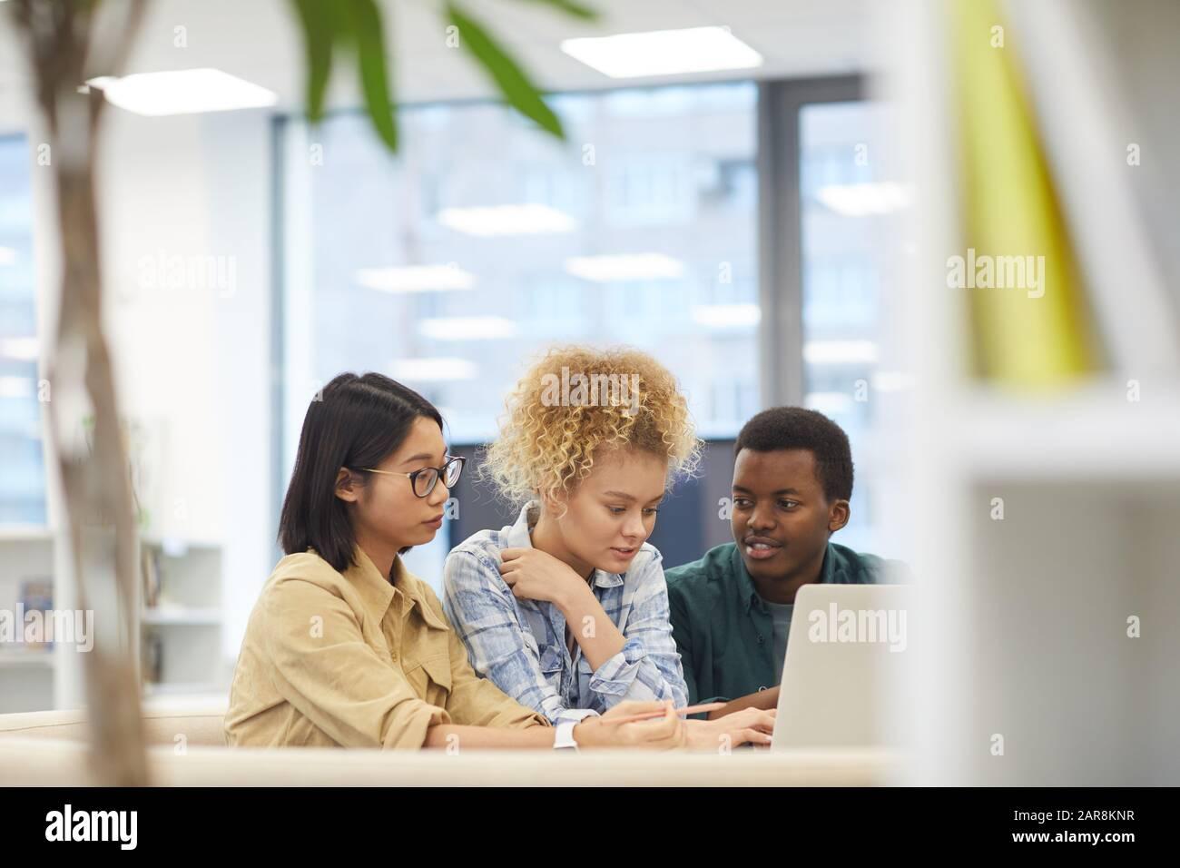 Portrait d'un groupe multi-ethnique d'étudiants utilisant ensemble un ordinateur portable tout en travaillant sur un projet dans la bibliothèque, espace de copie Banque D'Images