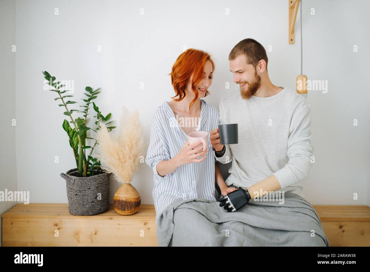 Heureux mari et femme assis ensemble sur une étagère, boire du café à la maison. Banque D'Images