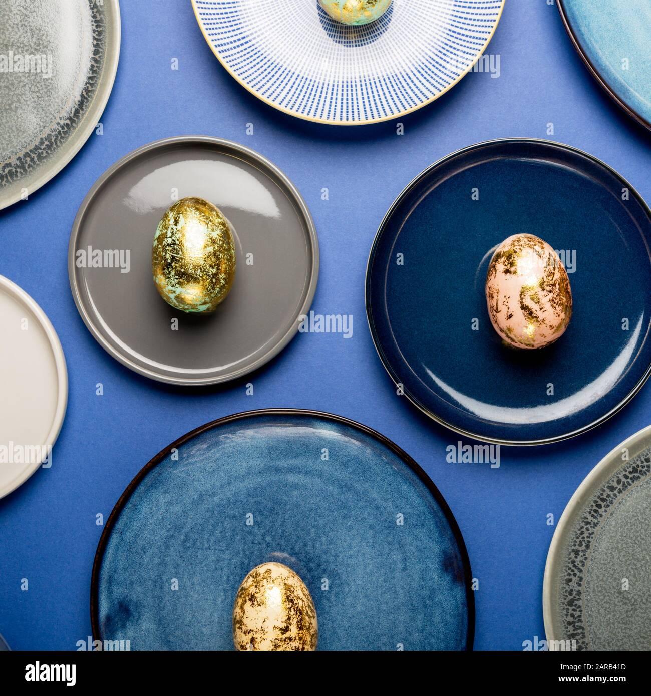 Plaques en céramique avec différents mouchetée d'or les oeufs de Pâques des tons pastels sur fond bleu. Happy Easter concept, design minimaliste, vue du dessus Banque D'Images