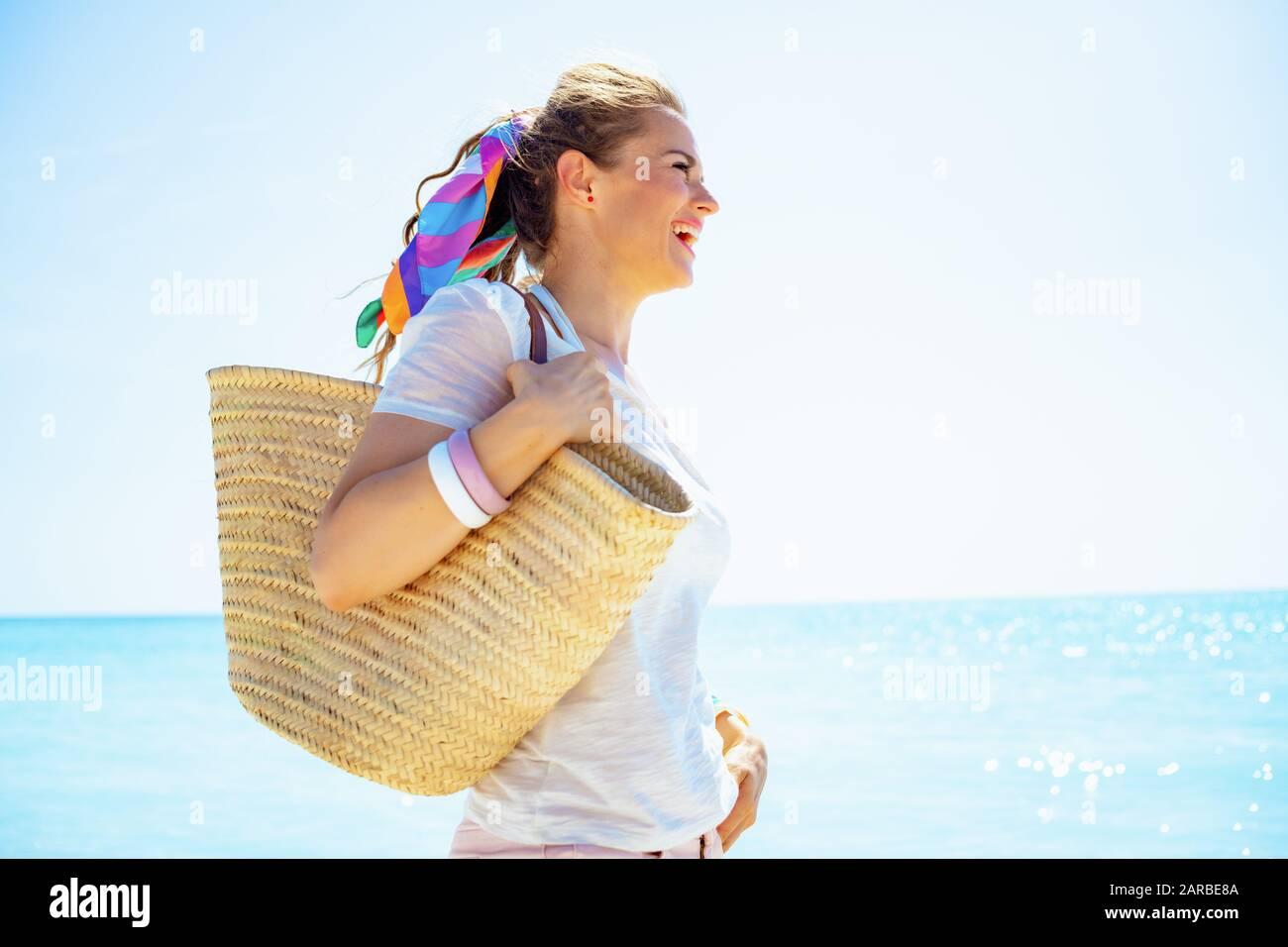 heureuse jeune femme dans un t-shirt blanc avec sac de paille de plage donnant sur la distance sur la rive de l'océan. Banque D'Images