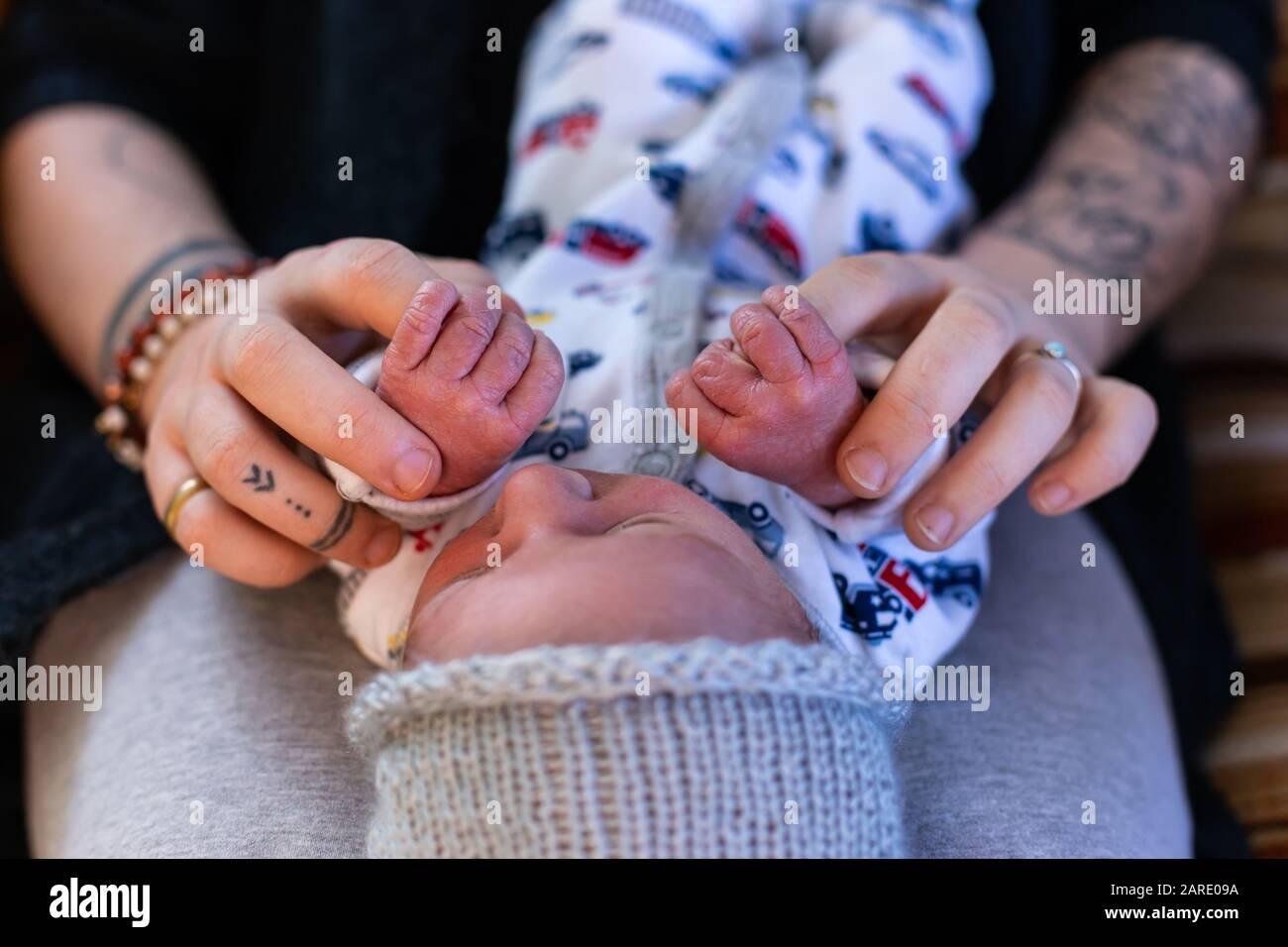 Une vue rapprochée et recadrée d'une nouvelle mère et d'un bébé garçon se liant à la maison, tenant les mains dans les jours après la naissance, beau moment de la parentalité. Copier l'espace sur les côtés Banque D'Images