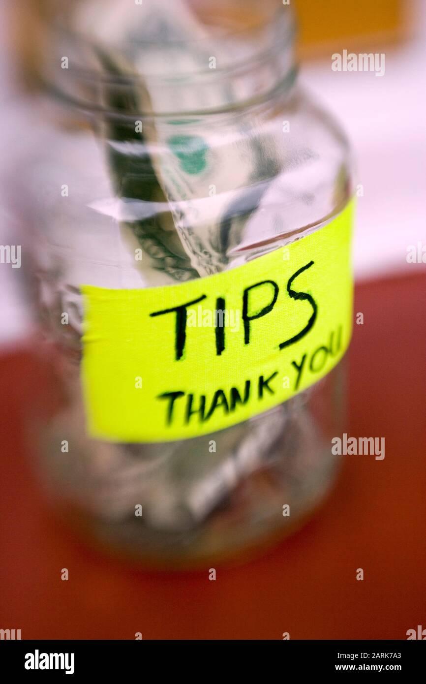 Toujours la vie d'un pot de pourboire avec des billets et des pièces de monnaie dans un restaurant local Banque D'Images