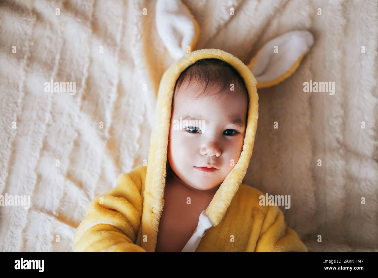 Un petit enfant avec un costume de lapin. Couché sur mauvais Banque D'Images
