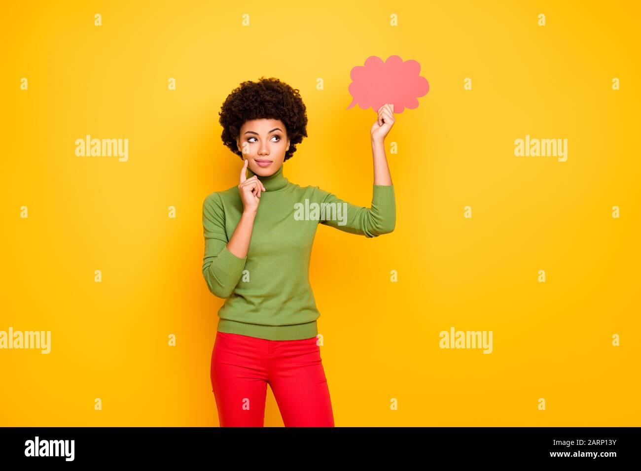 Photo de la pensée méditant la femme intéressée dans le pantalon rouge regardant dans le nuage rose de pensées pensant à de nouvelles idées isolé couleur de fond vibrante Banque D'Images