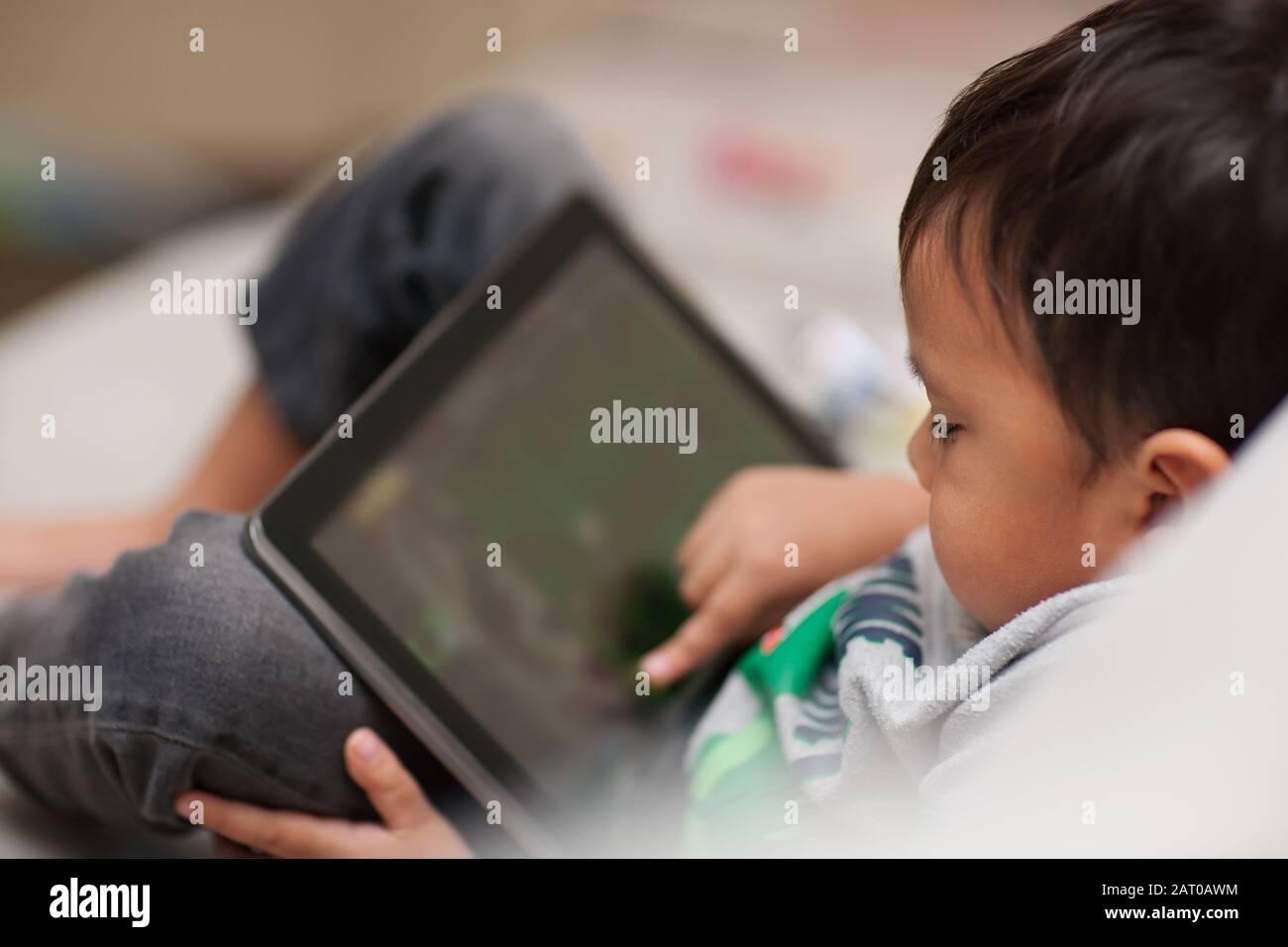 Un tout-petit non supervisé utilisant une tablette à la maison qui est détendu assis sur un canapé et à l'aide de son doigt sur l'écran tactile. Banque D'Images