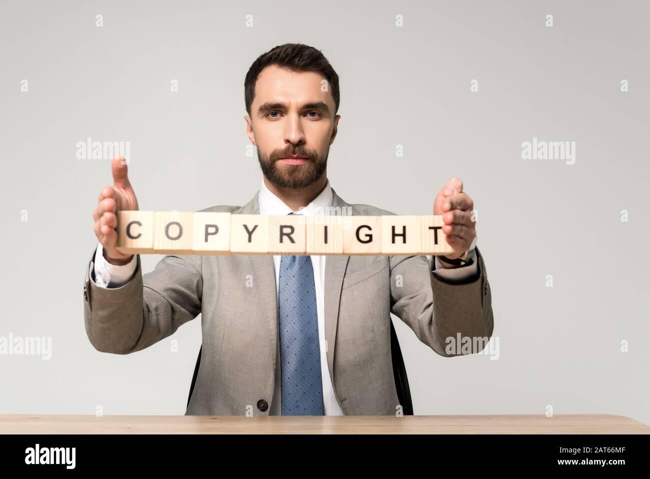 homme d'affaires confiant tenant des cubes de bois avec des lettres de copyright isolées sur gris Banque D'Images