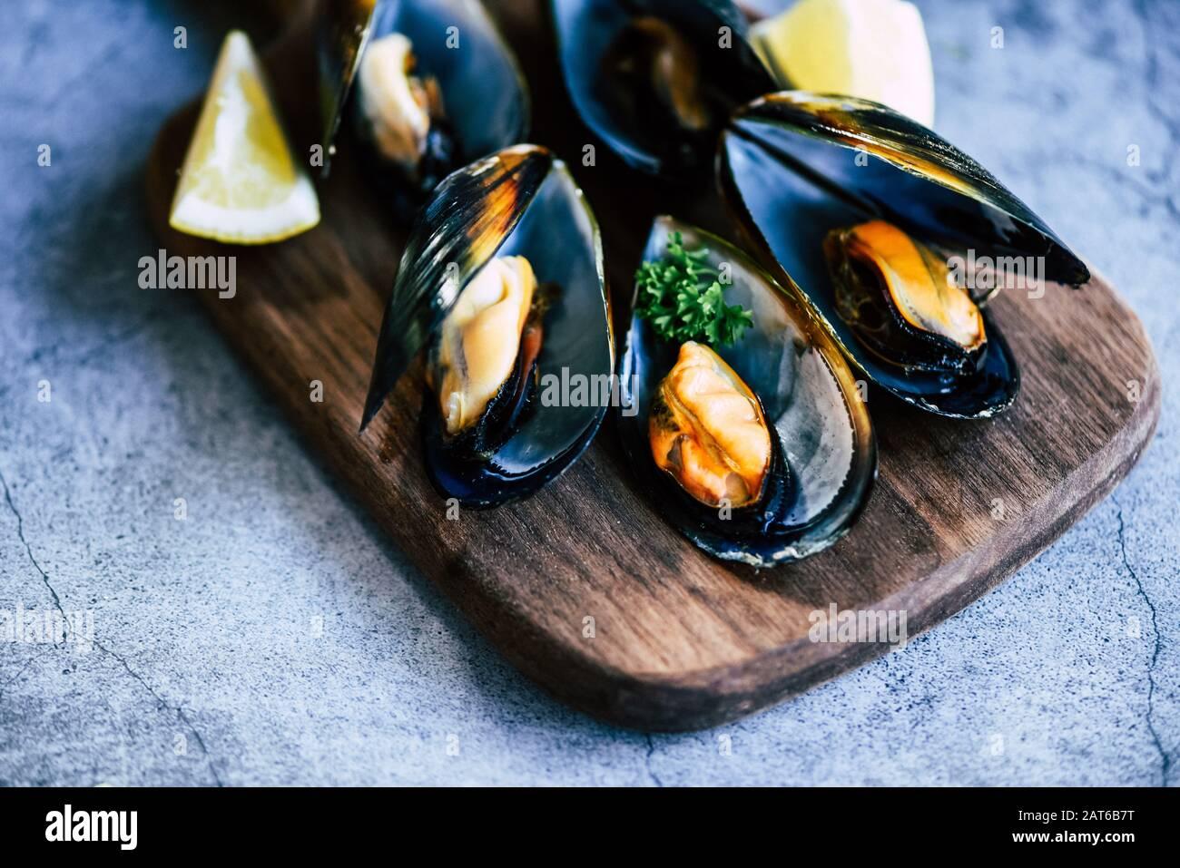 Moules cuites aux herbes fond de citron et de plaque sombre / fruits De mer Frais crustacés sur planche à découper en bois dans le restaurant moules shell alimentaire Banque D'Images