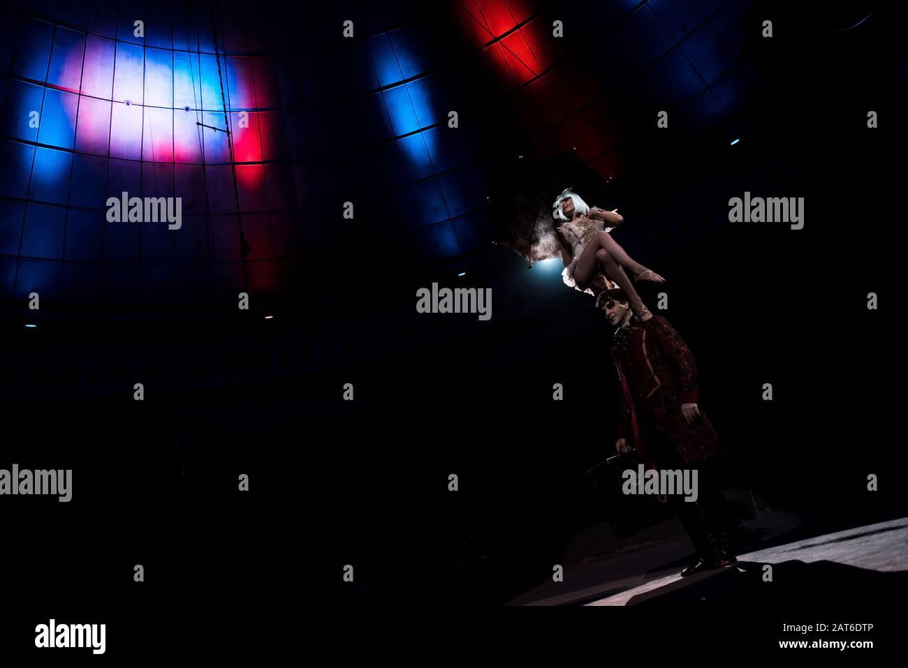 spectacle attrayant d'acrobat tout en étant assis sur le chapeau de l'homme dans le cirque Banque D'Images