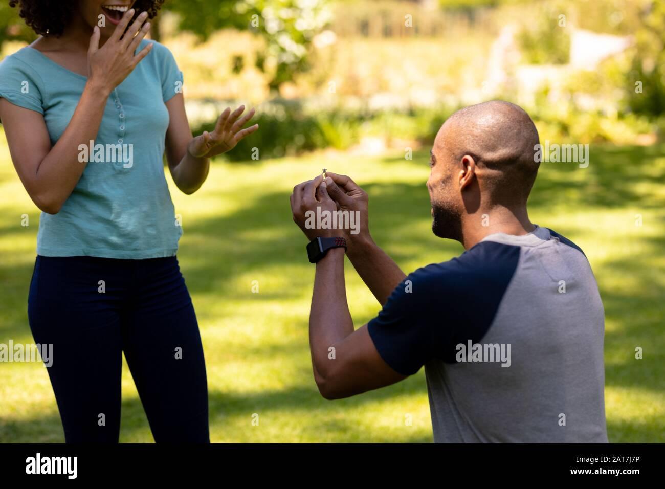 Jeune homme faisant la proposition de mariage dans le jardin Banque D'Images