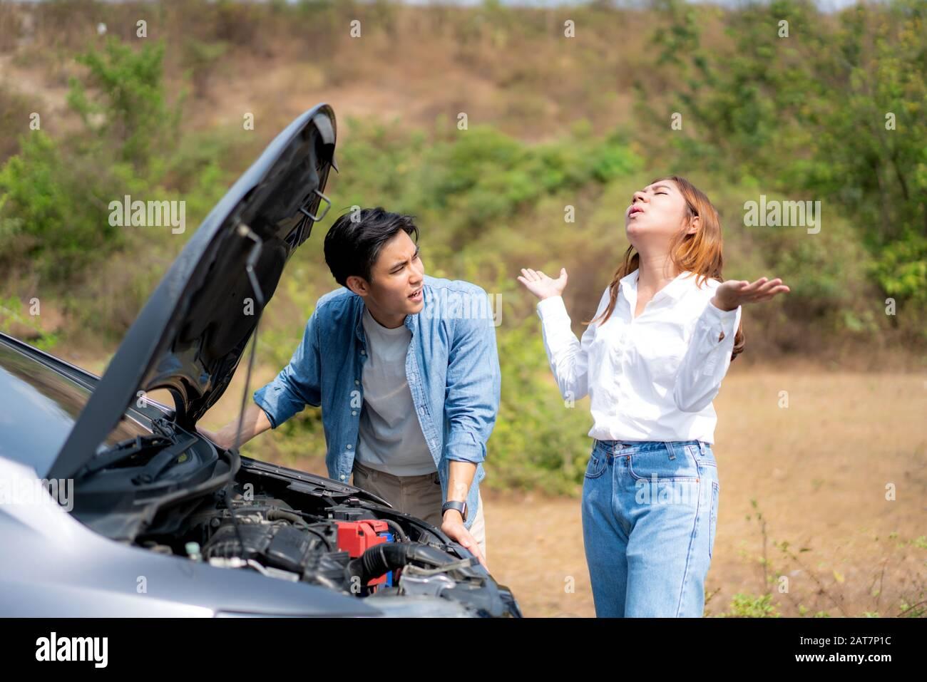Un jeune couple asiatique avec un homme et une femme sur la route ayant un problème de panne de moteur de voiture sur la route et une femme regardant le stress quand un homme ne peut pas se représenter Banque D'Images