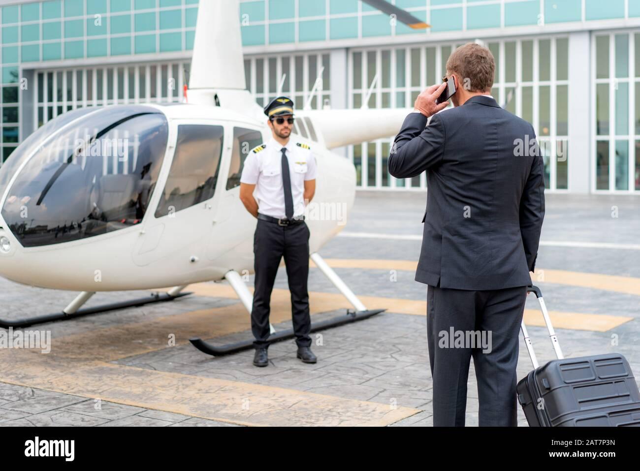 Homme d'Affaires âgé avec bagages parler téléphone mobile et marcher à l'hélicoptère pour le départ à destination à hélipad à l'aéroport avec hélicop Banque D'Images