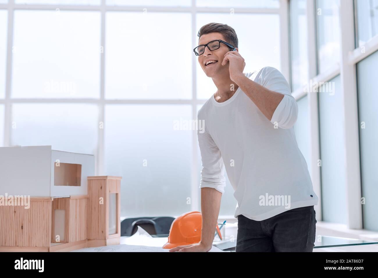 Concepteur réussi à parler sur son smartphone dans Design Studio. Banque D'Images