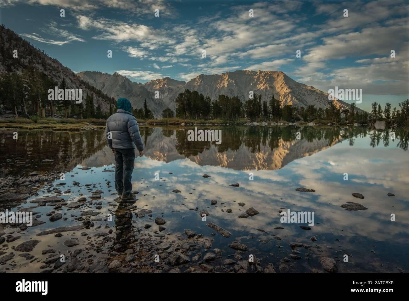 Homme regardant les réflexions de montagne dans Robinson Lake, Inyo National Forest, Californie, États-Unis Banque D'Images