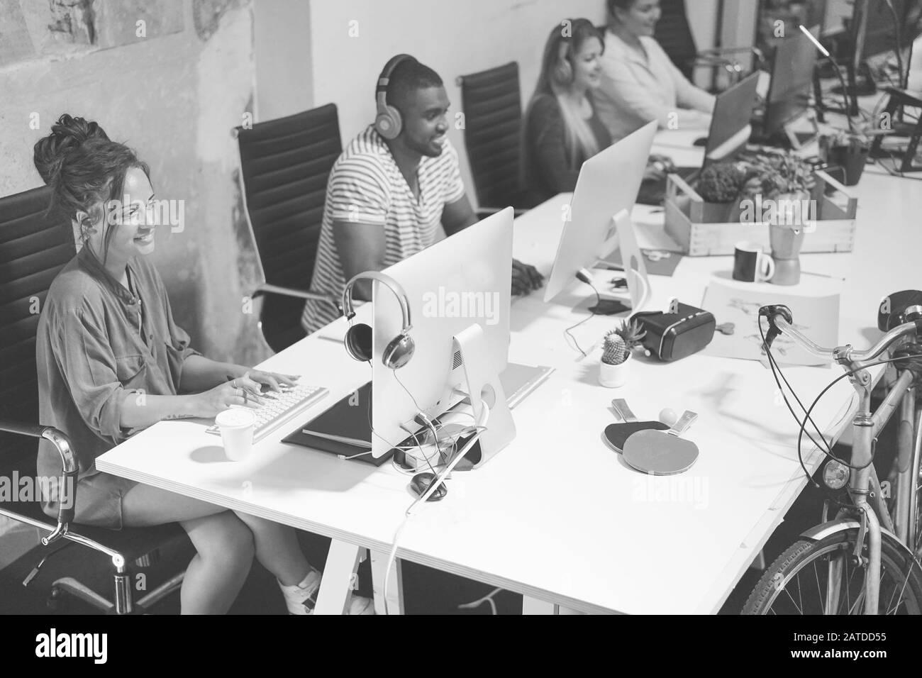 Travail d'équipe à la mode jeune utilisant l'ordinateur dans le bureau créatif - les gens d'affaires travaillant ensemble sur le projet de site Web - Focus sur femme à droite - Technolog Banque D'Images