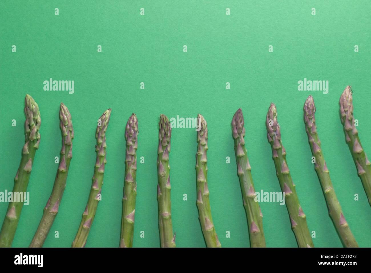 Asperges vertes brutes et saines sur fond vert. Detox et concept de super-alimentation. Banque D'Images