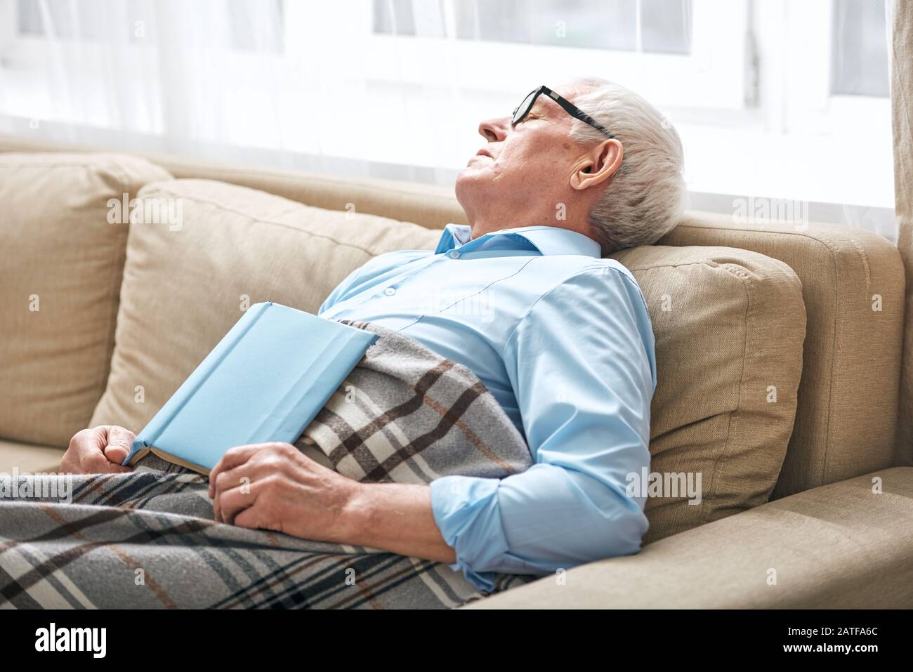 Homme senior fatigué couvert avec des aides au rodage sur le canapé avec livre ouvert Banque D'Images