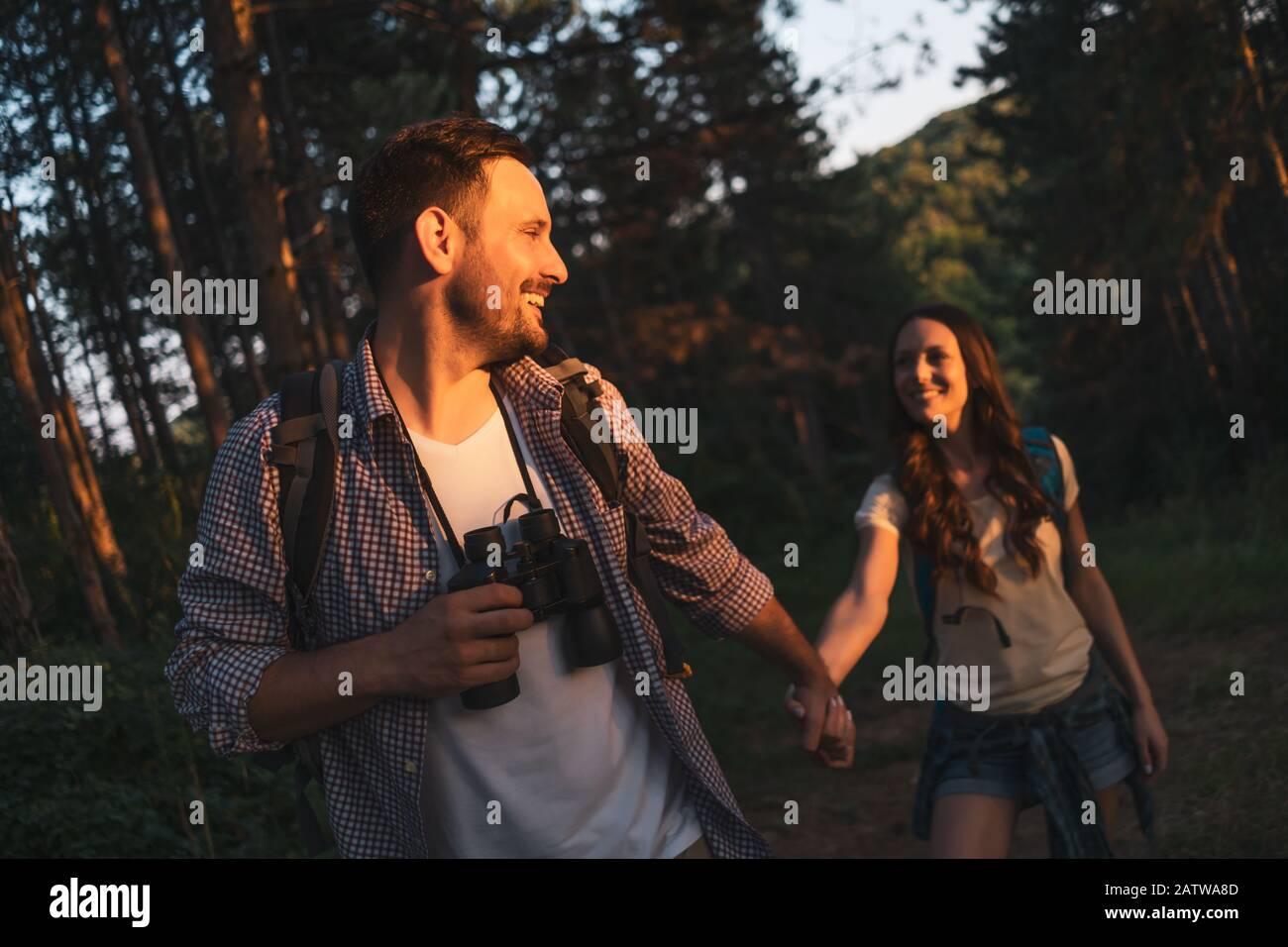 Un couple heureux fait de la randonnée dans la forêt l'après-midi. Banque D'Images